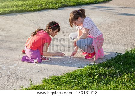yong girls drawing with chalk on the concrete playground for playing hopscotch