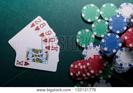 Casino chips and flush cards combination on the green table. Poker game
