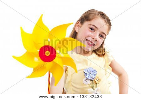 Smiling little girl holding a yellow pinwheel, isolated on white background