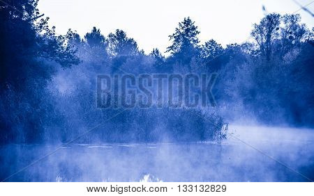 Morning fog on a calm river, tranquil scene on Severskiy Donets river, Ukraine, natural background with cold color toned image