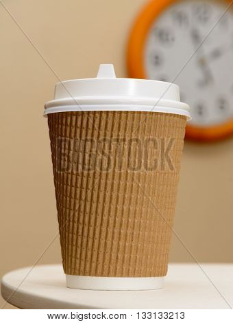 Coffee in brown paper cup on the clock background.