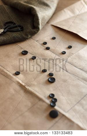 Atelier or Design Studio on tailoring. Patterns spilling buttons and scissors. Close up view.