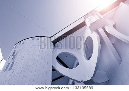 Perspective bottom view of concrete walls built in futuristic urban style. Architecture modern background with stylized cosmic reflected lights. Architecture cityscape in cold futuristic style.
