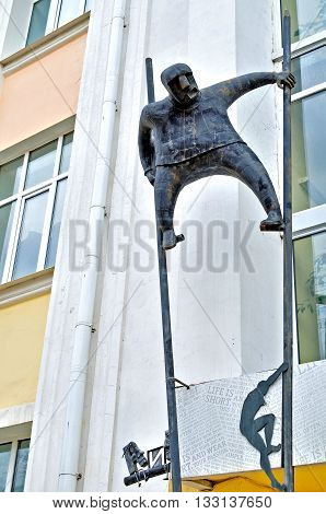 VELIKY NOVGOROD RUSSIA - APRIL 28 2016. Metal sculpture of man on stilts made in modern style at the facade of Novgorod center of contemporary art