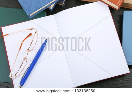 Open book, glasses and pen on table