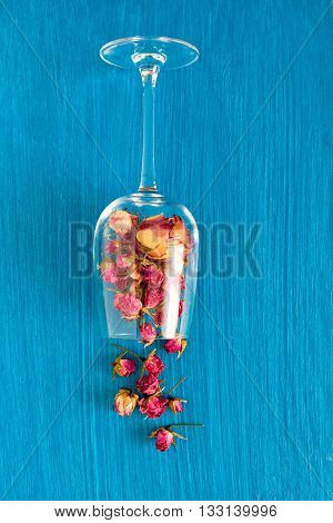 Dried pink roses in a glass goblet on a blue background. Concept card with space for your text or wallpaper background.