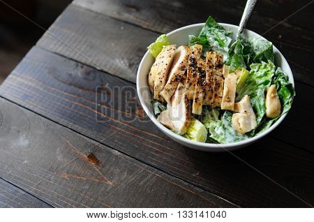 Chicken caesar salad in a white bowl on a wooden table