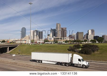 Truck on the highway with Dallas downtown skyline in the background. Texas United States