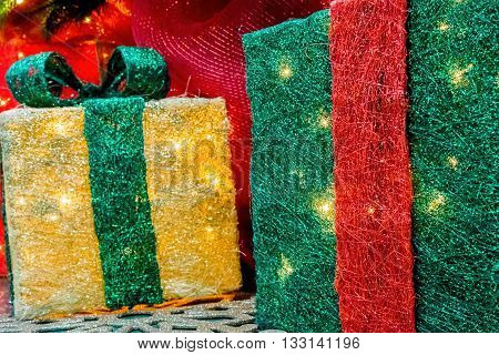 Christmas decorative boxes with internal warm lighting sitting on the floor, in among other ornaments. Closeup ground-level view.