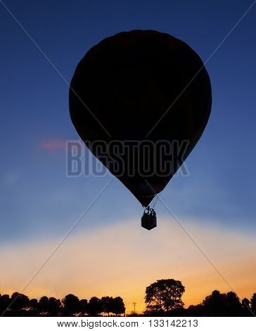 Silhouette of a hot air balloon trees power lines and distant spectators at sunset in the countryside.