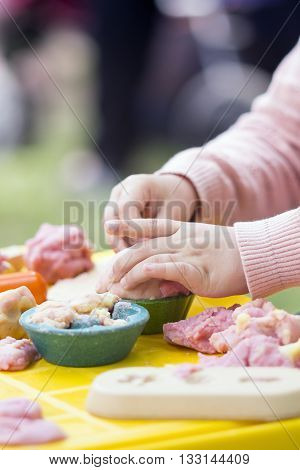 Child moulds from ecological plasticine on table. Hands with plasticine.