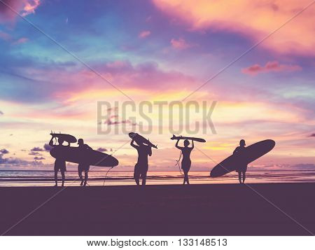 Silhouette Of surfer people carrying their surfboard on sunset beach vintage filter effect with soft style