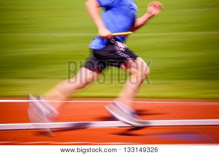 Blurred motion image of a man running in a relay race