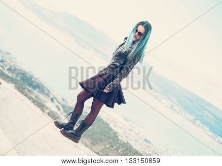Dark style beautiful young woman wearing in black leather jacket and dress standing on edge over the sea bay outdoor