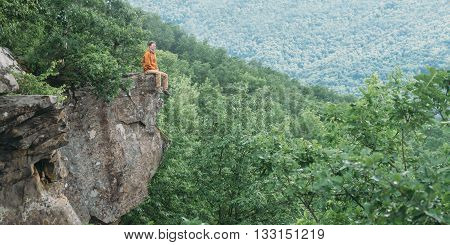 Traveler young man sitting on edge of cliff and enjoying view of nature in summer outdoor