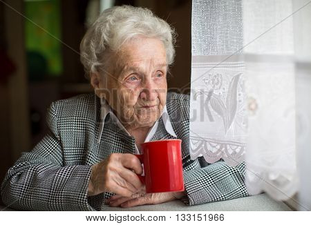 Elderly woman drinking tea sitting at the table.