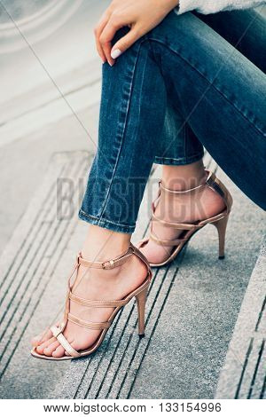 young woman sit on stairs in high heel golden sandals outdoor shot in the city