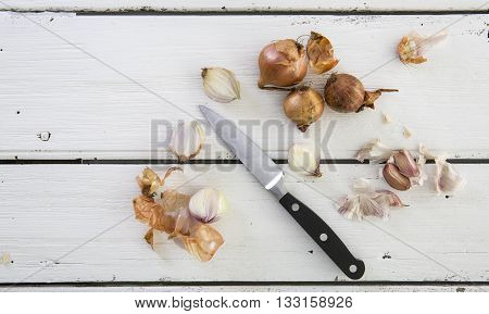 Shallots and Garlic with Knife on Rustic White Wooden Table