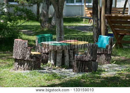 Stylized colorful wooden chairs and a table among the trees