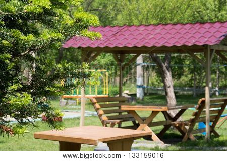 Wooden table and two benches with a canopy on the open air