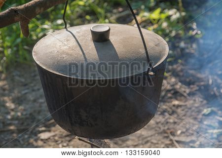 Old camping kettle over the fire. Closeup.