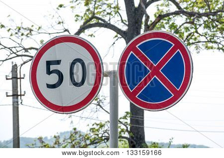 Two paired road sign. Speed limitation. Clouseup.