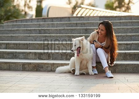 Pretty Vietnamese woman playing with her dog outdoors