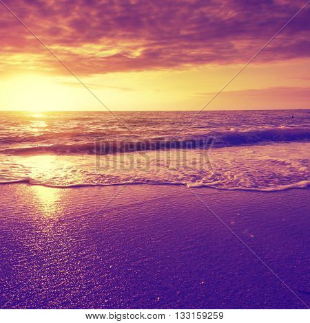 Dramatic sunset over sea and beach. Vintage image.
