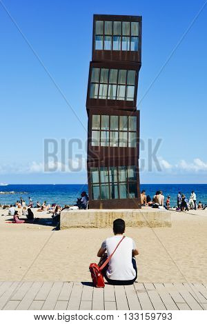 BARCELONA, SPAIN - MAY 30: People sunbathing at the Barceloneta Beach on May 30, 2016 in Barcelona, Spain. A sculpture designed by artist Rebecca Horn in COR-TEN steel presides over this urban beach
