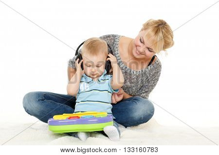 Young woman and her son are playing with developing toy on a white background. Happy family.
