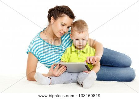 Young mother and her little son with computer tablet sit on a white background. Happy family.