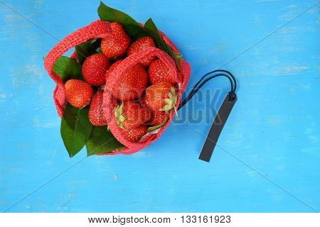 Basket with strawberries. Strawberries in a basket. Isolated on blue background. Red Basket.