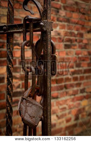 Rusty locks on the open gate of a concentration camp