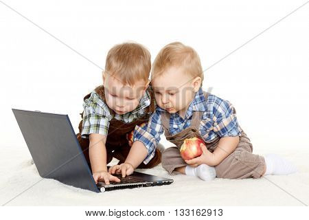 Two little boys with  with notebook and fresh apples sit on a floor on a white background.