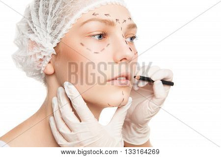 Close-up of unrecognizable plastic surgeon drawing marks on woman's face. Studio shot