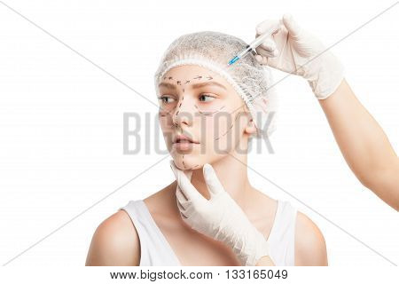 Portrait of young woman in medical hat being injected with syringe in face. Studio shot
