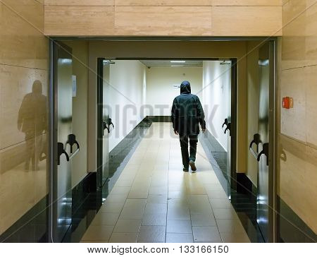 A man in a black jacket with a hood leaving a long corridor of the morgue