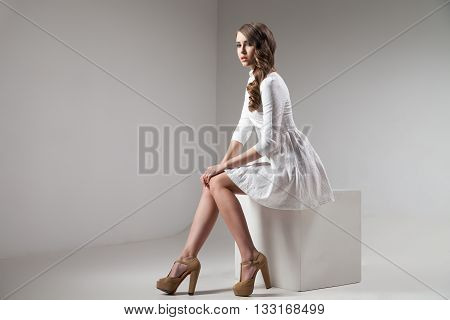 attractive girl in white dress on cube in studio