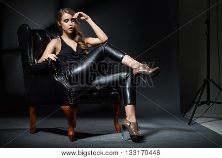 Beautiful young woman with make-up looking at camera while sitting on leather chair