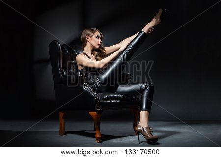 Brunette model in black chair with leg up.Studio shot