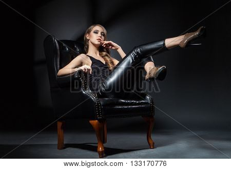 Beautiful young model with legs up posing on leather chair