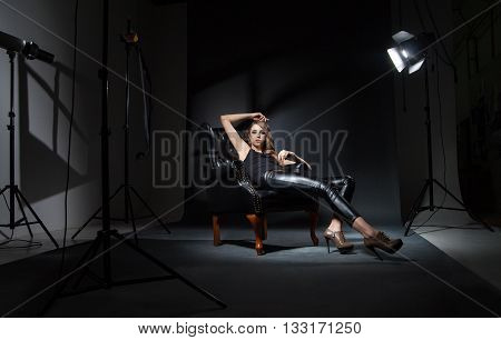 Interior of studio with model posing on leather chair