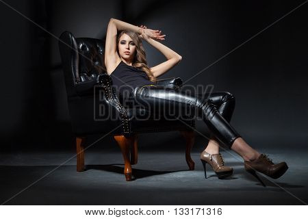 Portrait of attractive young girl in leather chair against of black background