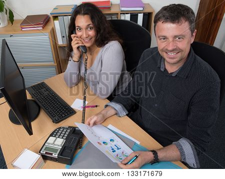Portrait Of Two Multi Ethnic Colleagues Working On Documents
