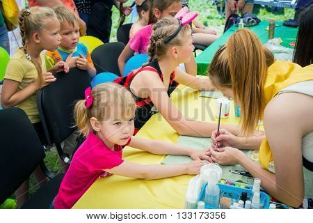 Zaporizhia/Ukraine- June 5, 2016: volunteer  painting nails of small girl during charity family festival organized in regions with most quantity of refugees from Donetsk area, occasioned with International Children`s Day