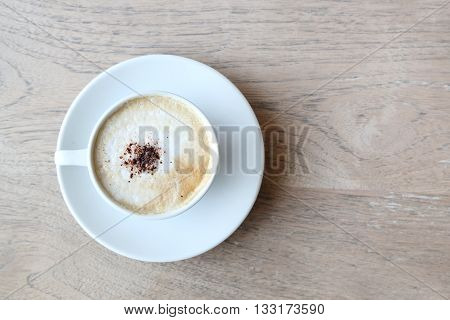 Cup of cappuccino with foam on the wooden table