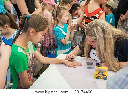 Zaporizhia/Ukraine- June 5, 2016: volunteer  painting flower on hand of a girl during charity family festival organized in regions with most quantity of refugees from Donetsk area, occasioned with International Children`s Day