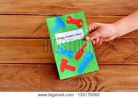Homemade fathers day greeting card idea. Child keeps a card in his hand. Child gives a gift. Handmade paper greeting card with different tools. Cool gift idea for dad. Paper work. Wooden background.