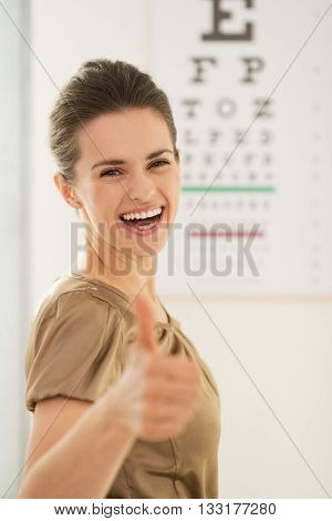 Happy Young Woman Showing Thumbs Up In Front Of Snellen Chart