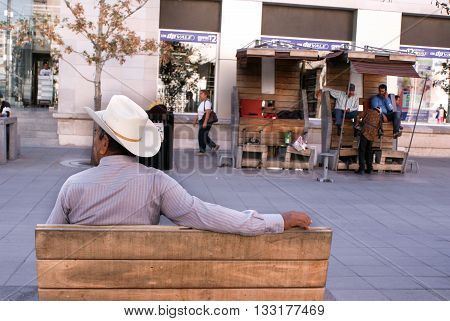 Chihuahua Mexico - October 8 2014: Mexican man wears a traditional white wide brim hat main street and shoe shiners on the background